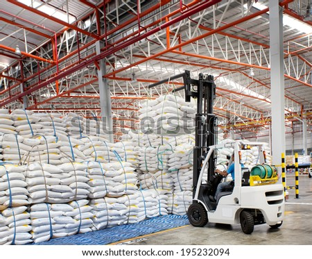 Forklift loader with big bag of sugar in distribution warehouse - stock photo