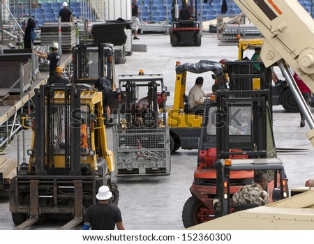 Forklift loaders and workers build stage - stock photo