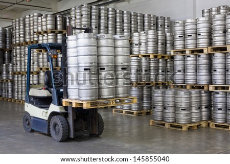 Forklift loading beer kegs in warehouse brewery  - stock photo