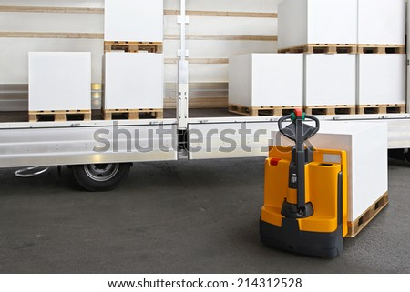 Forklift loading pallets with paper in truck - stock photo