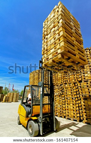 Forklift operator lifting bunch of euro pallets  - stock photo
