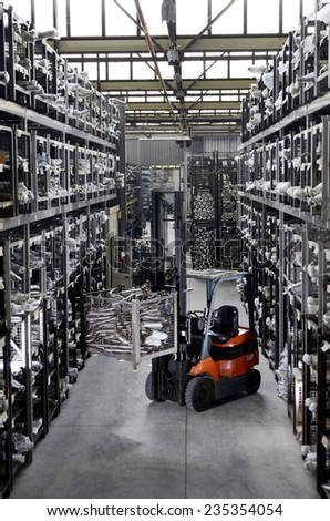 Forklift pallet truck in the narrow aisle goods warehouse, with load palletising of car mufflers. A fork lift truck moves stacked pallets inside an metal warehouse. - stock photo