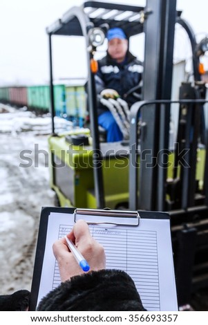 Forklift stands at the entrance to warehouse. Hand of woman makes a record delivery of goods