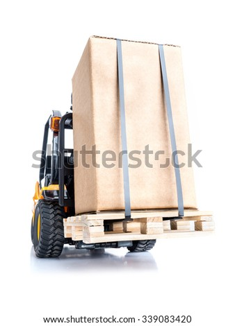 Forklift truck carrying goods packed in cardborad box placed on wooden pallet shot on white background - stock photo