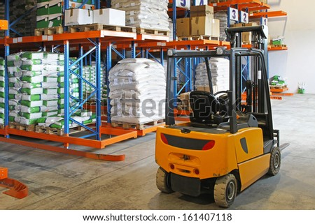 Forklift truck in distribution warehouse with racks