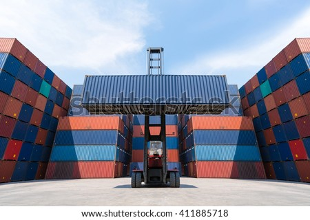 Forklift truck lifting cargo container in shipping yard for import,export, logistic industrial with container stack background  - stock photo