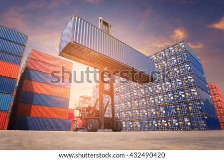 Forklift truck lifting cargo container in shipping yard or dock yard against sunrise sky with cargo container stack in background for transportation import,export and logistic industrial concept - stock photo
