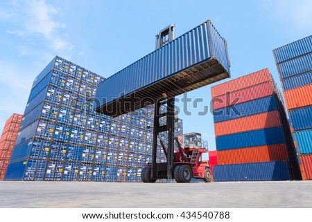 Forklift truck lifting cargo container in shipping yard or dock yard with cargo container stack in background for transportation import,export and logistic industrial concept - stock photo