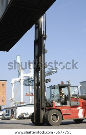 forklift truck lifting container with commercial port in background