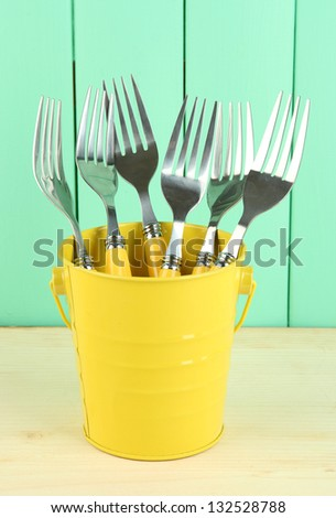 Forks in metal bucket on color wooden background - stock photo