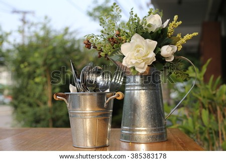 Forks, knifes and spoons in vintage style zinc cutlery holder and artificial flowers in zinc watering can, Set on wooden table. - stock photo