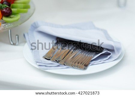 Forks lie under a white napkin on the plate