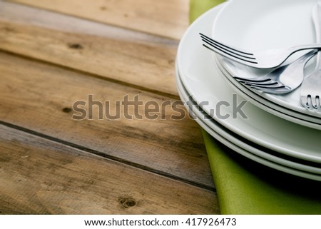 Forks on stacked plates with napkin on a reclaimed wood table. Food, restaurant, healthy eating, dining and interior design concept