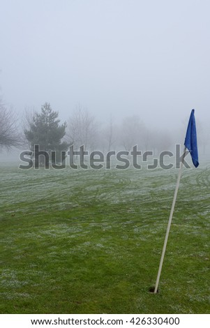 Forlorn looking flag on an empty golf course on a cold and foggy day - stock photo