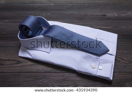 Formal blue shirt and necktie on wooden table - stock photo