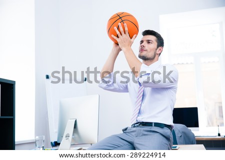 Formal businessman sitting on the table with ball in office - stock photo
