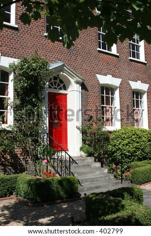 Formal gardens and frontage of Georgian house - stock photo