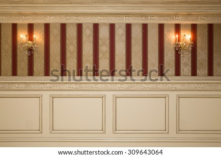 Formal interior wall with wallpaper, sconces and paneling  - stock photo