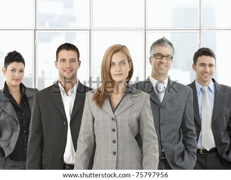 Formal portrait of happy business team standing in office, smiling.?