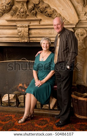 Formal portrait of older senior couple in an old hotel reception with large ornate fireplace - stock photo