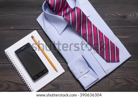 formal shirt and tie on black wooden table and spiral notebook and smartphone and pencil - stock photo