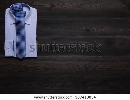 formal shirt and tie on wooden table top with copyspace, top view (view from above) - stock photo