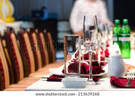 Formal stylish setting on a dinner table with elegant glassware and red linen for a party or celebration of a special event - stock photo