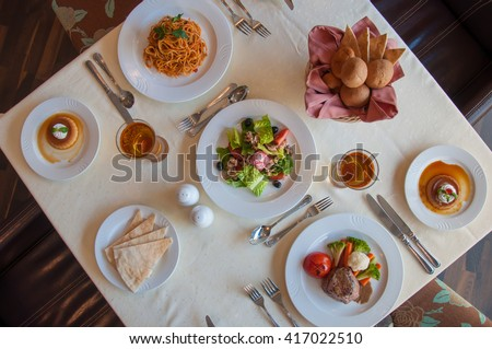 Formal table setting in the fine dining restaurant. International cuisine spread. View from top. - stock photo