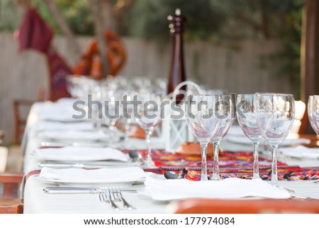 Formal table setting with elegant glassware and linen at an outdoor BBQ in celebration of a special event - stock photo