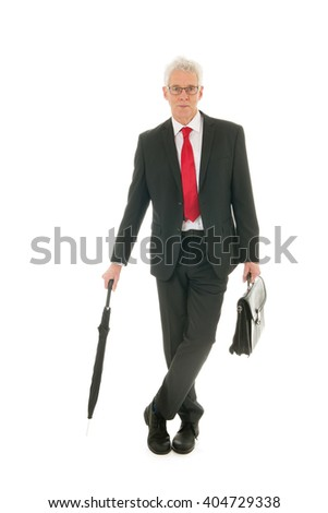 Formally dressed Senior business man with umbrella and case - stock photo