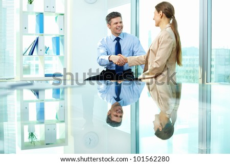 Formally dressed young people handshaking after making agreement in office - stock photo