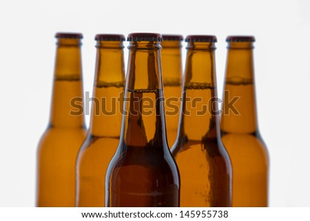 Formation of beer bottles A formation of six brown beer bottles with a white background