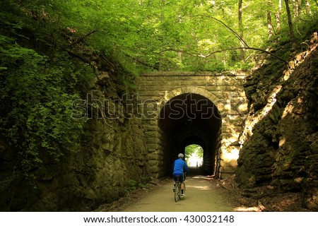 Former railroad tunnel built along the Missouri River; man biking toward the tunnel - stock photo