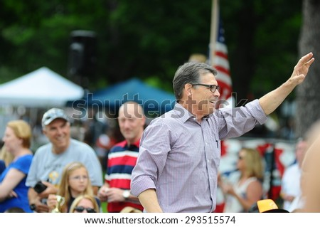 Former Texas Governor Rick Perry waves to the crowd during the July 4 parade in Amherst, New Hampshire, on July 4, 2015. - stock photo