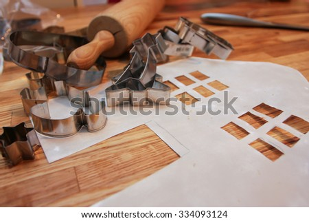 forms and designs for gingerbread cookies and house on a table ready for use