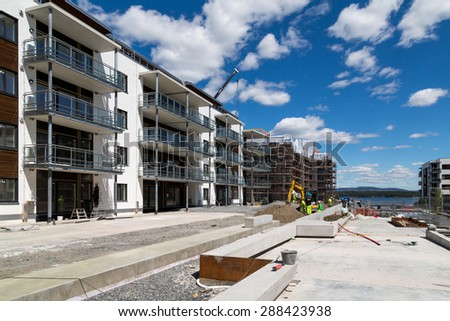 Fornebu, Oslo, Norway, 15 June 2015. Construction workers building luxury apartments on the fjord. The area around the old airport has been converted to high tech offices and new homes - stock photo