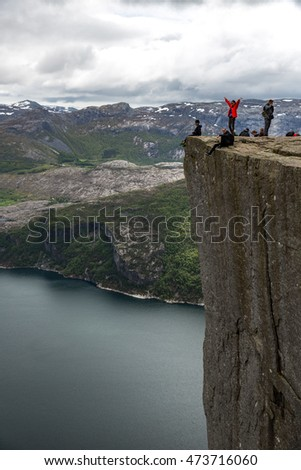 Forsand, Norway - June 15, 2015: Tourists climbing the Preikestolen, or Pulpit Rock, a steep cliff which rises 604 metres (1982 feet) above Lysefjorden in Norway.