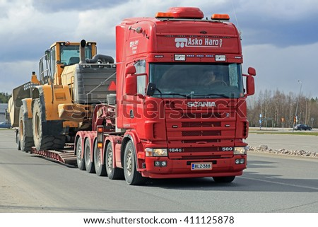 FORSSA, FINLAND - APRIL 23, 2016: Scania 164G transports heavy Volvo L350F wheel loader as wide load in South of Finland. - stock photo