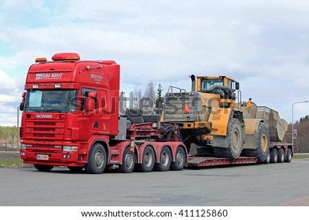 FORSSA, FINLAND - APRIL 23, 2016: Scania 164G truck stops at a truck stop during the oversized transport of heavy Volvo L350F wheel loader.