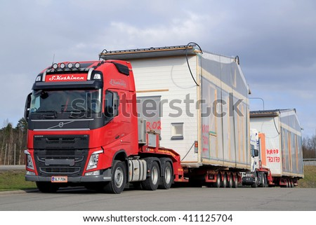 FORSSA, FINLAND - APRIL 23, 2016: Volvo FH semi and another truck are ready to transport prefabricated house modules as oversize loads in South of Finland. - stock photo
