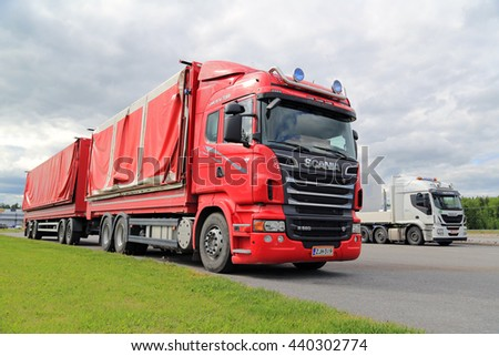 FORSSA, FINLAND - JUNE 21, 2015: Red Scania R560 with side dumping trailer parked at a truck stop with green grass, grey sky and white Iveco truck on the background.  - stock photo
