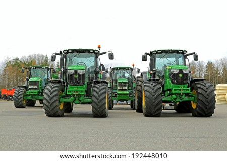 FORSSA, FINLAND - MAY 10, 2014: Four John Deere agricultural tractors, two of 6210R on the front, 7530 and 6820 on the back. John Deere's Manure Sensing System is awarded at the FIMA 2014 show. - stock photo