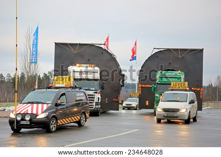 FORSSA, FINLAND - NOVEMBER 30, 2014: Pilot cars and two Scania trucks with oversize loads. One pilot vehicle with height measuring pole is required, if the load exceeds 5 m in height. - stock photo