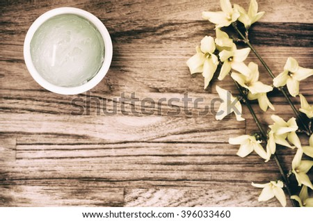 forsythia flowerd twig ans decorations on a natural wood surafce - copy space - stock photo