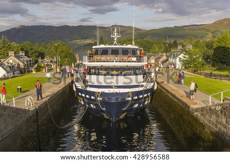 FORT AUGUSTUS, SCOTLAND - AUGUST 22, 2004: Cruise ship move through locks from Loch Ness toward Loch Lochy, Caledonia Canal, in the Highlands. - stock photo