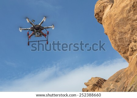 FORT COLLINS, CO, USA, February 12,  2015:  F550 Flame Wheel  hexacopter drone is  flying with a camera along sandstone cliff. - stock photo