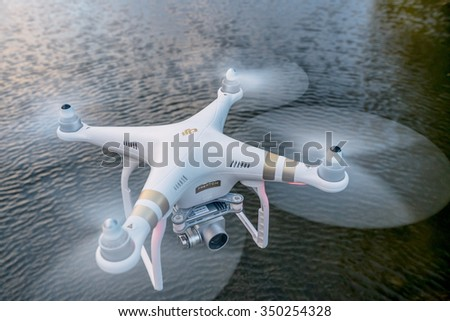 FORT COLLINS, CO, USA, October 18, 2015:  Radio controlled Phantom 3 quadcopter drone flying with a camera over a lake. - stock photo