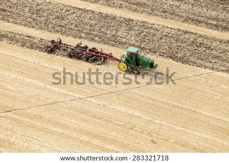Fort Hall, Idaho, USA Aug. 18, 2012 A tractor in the plowing a farm field in preparation for spring planting. - stock photo