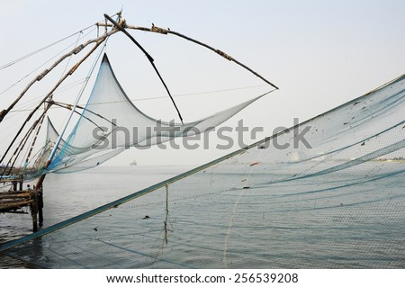 FORT KOCHI, INDIA - 16 JANUARY 2015: fishermen operate a Chinese fishing net based on ancient technology and traditional materials, ropes and stones at Fort Kochi, Kerala, India - stock photo