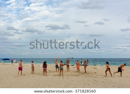 FORT LAUDERDALE BEACH, FL - JANUARY 13: Young people playing a game of beach volleyball in Ft. Lauderdale, Florida on January 13, 2016 - stock photo